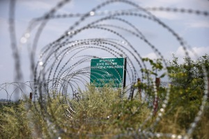 A warning sign is pictured behind a wire barricade erected by Russian and Ossetian troops along Georgia's de-facto border with its breakaway region of South Ossetia in the village of Khurvaleti, Georgia, July 14, 2015. Georgia accused Russia on Monday of violating its sovereignty by placing border markers on the edge of the South Ossetia region, leaving part of an international oil pipeline in territory under Russian control. REUTERS/David Mdzinarishvili - RTX1K9UA